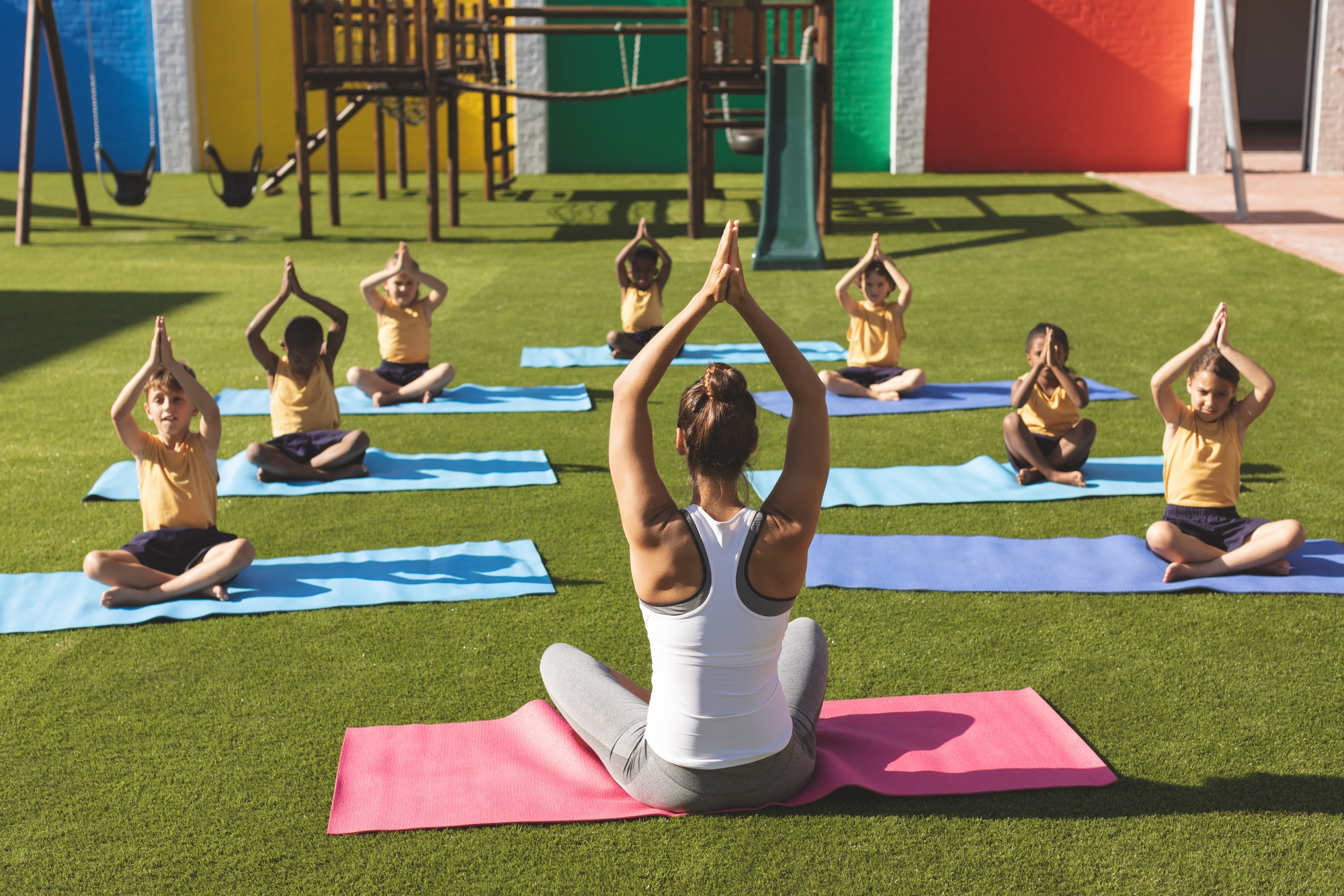 Trainer teaching yoga to students in yoga mat in school playground at schoolyard